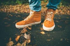 脚走在秋天的运动鞋留给室外 免版税库存照片