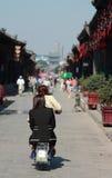脚踏车的妇女在平遥老镇  免版税库存照片