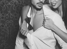 脱下衣服时髦强壮男子的人室内黑白的性感的妇女 免版税库存照片