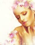 脸色 有完善的被镀青铜的皮肤和兰花花的华美的妇女 芬芳 免版税库存照片