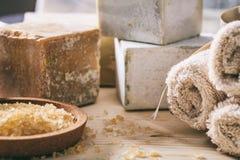 腌制槽用食盐、毛巾和肥皂在木背景 免版税库存照片