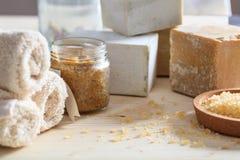 腌制槽用食盐、毛巾和肥皂在木背景 免版税库存图片