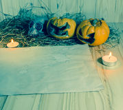腐烂的万圣夜南瓜和老纸与烛光和烘干 免版税图库摄影