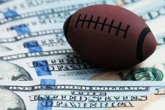 腐败或体育打赌的概念 橄榄球或橄榄球的标志的特写镜头在一百美元背景  库存照片