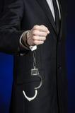 腐败和贿赂题材:在一套黑衣服的商人与在他的手上的手铐在深蓝背景在被隔绝的演播室 库存图片
