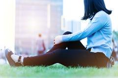 腕子手痛苦妇女坐绿草在日落的,城市生活方式概念操场 库存图片