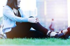 腕子手痛苦妇女坐绿草在日落的,城市生活方式概念操场 免版税库存照片