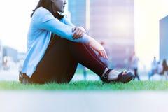 腕子手痛苦妇女坐绿草在日落的,城市生活方式概念操场 图库摄影