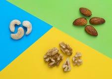 腰果、杏仁和核桃在蓝色,绿色和黄色背景 免版税库存图片