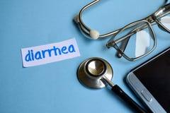 腹泻题字有听诊器、镜片和智能手机看法在蓝色背景 图库摄影