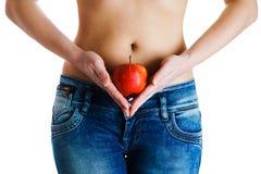 腹部女性 拿着红色苹果的妇女手 IVF,怀孕,饮食概念 库存照片