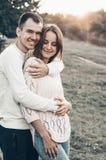 腹部孕妇 加上握手的孕妇在浪漫大气的日落在夏时 免版税库存照片
