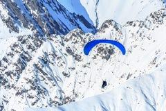 腾飞反对多雪的山峰的纵排滑翔伞 极端prarglide冬天飞行 免版税库存照片