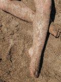 腿和脚在沙子 免版税库存照片