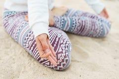 腿坐沙子,莲花坐的女孩,手指 免版税库存图片
