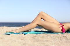 给腿打蜡的秀丽完善的妇女晒日光浴在海滩 库存照片