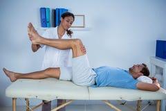 给腿按摩的生理治疗师患者 免版税库存图片