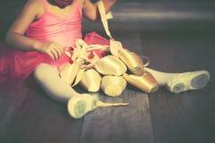 腿有芭蕾pointe鞋子和桃红色裙子的一位小芭蕾舞女演员 免版税图库摄影