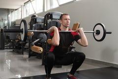 腿的前面杠铃蹲坐锻炼 免版税图库摄影