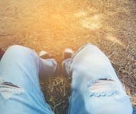 腿的顶视图在牛仔裤和运动鞋的在草 图库摄影