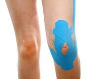 腿的治疗治疗有蓝色理疗的磁带的 图库摄影