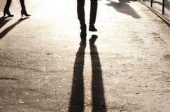 腿Defocused阴影和剪影在城市边路的 免版税库存照片