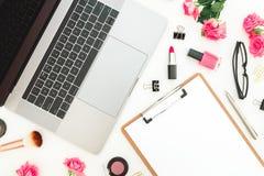 膝上型计算机、剪贴板、玫瑰花、化妆用品和辅助部件在白色背景 平的位置 顶视图 女性自由职业者compositi 免版税库存照片