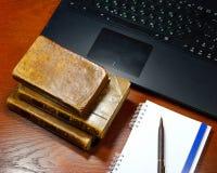 膝上型计算机、古色古香的书和笔记本 免版税库存照片