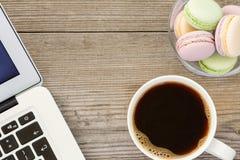 膝上型计算机、咖啡和法国macarons 免版税库存图片