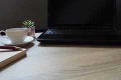 膝上型计算机、咖啡和花在木桌上在一个工作场所早晨 免版税库存照片