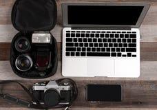 膝上型计算机、巧妙的电话、照片照相机和耳机在木背景 免版税库存照片