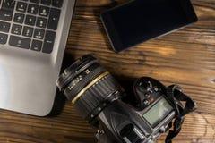 膝上型计算机、巧妙的电话和照片照相机在木背景 库存图片