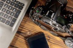 膝上型计算机、巧妙的电话和照片照相机在木背景 免版税图库摄影