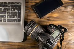 膝上型计算机、巧妙的电话和照片照相机在木背景 图库摄影