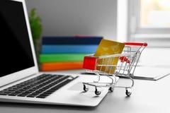 膝上型计算机、微型市场台车和信用卡在桌上 免版税库存照片