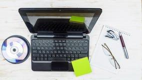 膝上型计算机、恶疾病人盘、笔记薄、玻璃、订书机和笔在木头 免版税图库摄影