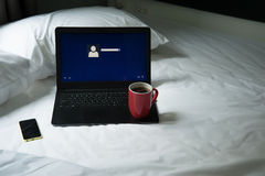 膝上型计算机、手机和一杯咖啡在床上的 免版税库存图片