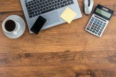 膝上型计算机、手机和咖啡杯在工作书桌上 免版税图库摄影