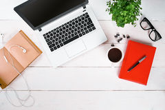 膝上型计算机、数字式片剂、日志、咖啡杯和盆的植物在工作书桌上 库存照片