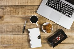 膝上型计算机、日志和早餐在木背景 库存照片