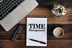 膝上型计算机、时钟、玻璃、咖啡和笔记本有时间安排词的在一张木桌上 库存图片