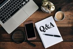 膝上型计算机、时钟、电话、放大镜、咖啡和笔记本有Q&A词的 库存图片