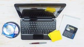 膝上型计算机、激光盘、笔记薄计算器和钢笔 库存图片