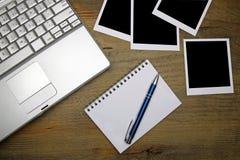 膝上型计算机、照片框架和笔记本有笔的在老木书桌上 免版税库存图片