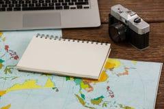 膝上型计算机、照相机、笔记薄和地图特写镜头  库存图片