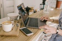 膝上型计算机、电话和咖啡和女孩` s手 在轻的caffee的工作 免版税库存图片