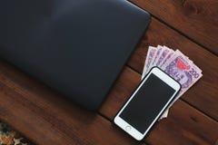 膝上型计算机、电话和金钱在木背景 免版税库存照片