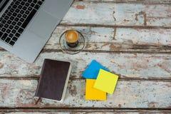 膝上型计算机、稠粘的笔记和日志与咖啡 库存图片