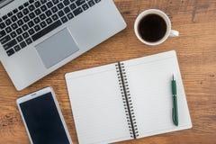 膝上型计算机、笔记本、片剂和咖啡在工作书桌上 免版税库存照片