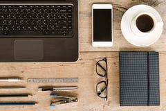 膝上型计算机、笔记本、电话、咖啡、玻璃、笔和铅笔在木办公桌上 免版税库存图片